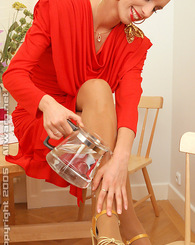 Blonde babe is a sexy red dress pours water all over herself